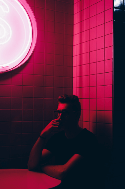 Someone in the shadow in a room with pink light